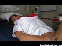 Pielęgniarka palcuje się na łóżku pacjenta